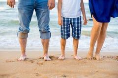 Adultos del pie y un niño en la playa Fotos de archivo