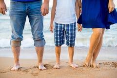 Adultos del pie y un niño en la playa Imágenes de archivo libres de regalías