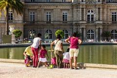 Adultos e crianças que relaxam nos jardins de Luxemburgo Paris, F Imagem de Stock