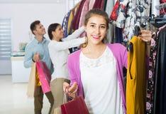 Adultos en buenas compras del humor en la tienda de ropa Imágenes de archivo libres de regalías