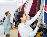 Adultos en buenas compras del humor en la tienda de ropa Fotos de archivo