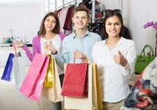 Adultos en el buen humor que celebra bolsos en la tienda de ropa Fotografía de archivo libre de regalías