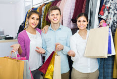 Adultos en el buen humor que celebra bolsos en la tienda de ropa Imagen de archivo libre de regalías