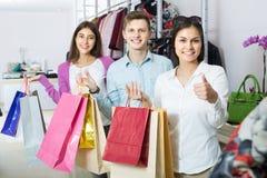 Adultos en el buen humor que celebra bolsos en la tienda de ropa Foto de archivo libre de regalías