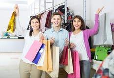 Adultos en el buen humor que celebra bolsos en la tienda de ropa Imagen de archivo