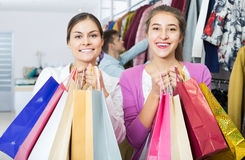 Adultos en el buen humor que celebra bolsos en la tienda de ropa Foto de archivo