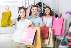 Adultos en el buen humor que celebra bolsos en la tienda de ropa Fotos de archivo