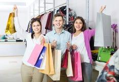 Adultos en el buen humor que celebra bolsos en la tienda de ropa Fotos de archivo libres de regalías