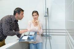 Adultos felices de los pares que eligen la baldosa cerámica para el cuarto de baño Fotos de archivo libres de regalías