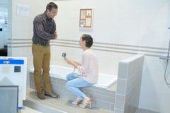 Adultos felices de los pares que eligen los grifos del cuarto de baño en tienda de la fontanería Fotografía de archivo libre de regalías