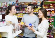 Adultos felices que eligen la comida enlatada Fotos de archivo libres de regalías