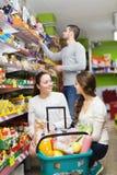Adultos felices que eligen la comida enlatada Imagen de archivo libre de regalías