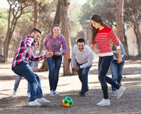 Adultos felices que persiguen la bola al aire libre Foto de archivo