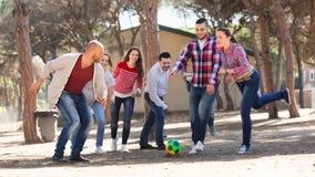 Adultos felices que persiguen la bola al aire libre Fotografía de archivo libre de regalías
