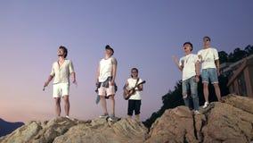 Adultos jovenes asiáticos que cantan encima de rocas almacen de video