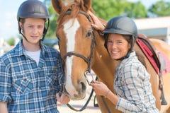 Adultos jovenes con el caballo Foto de archivo libre de regalías