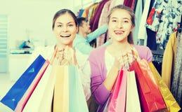 Adultos jovenes con las compras en tienda Imágenes de archivo libres de regalías