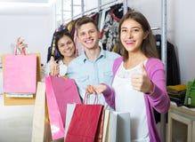 Adultos jovenes con las compras en tienda Foto de archivo libre de regalías