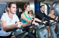 Adultos jovenes en las bicicletas estáticas en gimnasio Fotografía de archivo