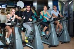 Adultos jovenes en las bicicletas estáticas en gimnasio Foto de archivo libre de regalías