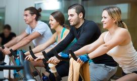 Adultos jovenes en las bicicletas estáticas en gimnasio Imagen de archivo libre de regalías