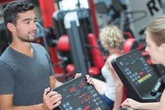 Adultos jovenes en las máquinas en club de fitness Imagenes de archivo