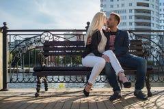 Adultos jovenes hombre y mujer en un banco en la ciudad Fecha romántica Foto de archivo libre de regalías