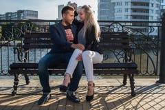 Adultos jovenes hombre y mujer en un banco en la ciudad Fecha romántica Foto de archivo
