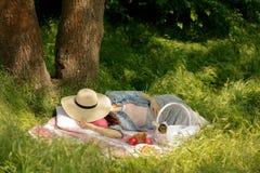 Adultos jovenes La mujer joven está descansando sobre una comida campestre en un bosque en a foto de archivo libre de regalías