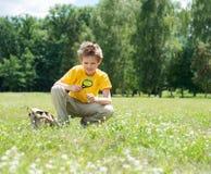 Adultos jovenes Muchacho feliz con la lupa al aire libre Foto de archivo