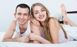 Adultos jovenes positivos que mienten en cama de la familia Imagenes de archivo