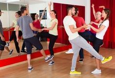 Adultos jovenes que bailan en un estudio Foto de archivo