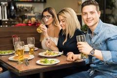 Adultos jovenes que beben la cerveza en un restaurante Imagen de archivo libre de regalías