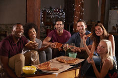 Adultos jovenes que comen la pizza en una mirada del partido a la cámara fotografía de archivo