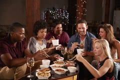 Adultos jovenes que comen para llevar chino en un partido en casa Imagenes de archivo