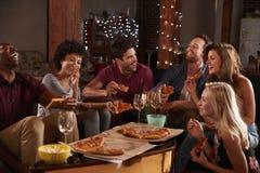 Adultos jovenes que comparten las pizzas en un partido en casa fotos de archivo
