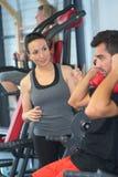 Adultos jovenes que hacen powerlifting en las máquinas en el club de fitness Fotos de archivo libres de regalías