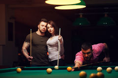 Adultos jovenes que juegan al juego del billar en club oscuro Fotos de archivo libres de regalías