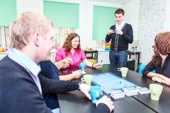 Adultos jovenes que pasan tiempo en el juego de adivinanzas emocionante Imagen de archivo libre de regalías