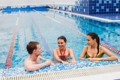 Adultos jovenes que se divierten que habla en piscina dentro Foto de archivo