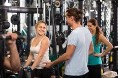 Adultos jovenes que se resuelven en club de fitness Imágenes de archivo libres de regalías