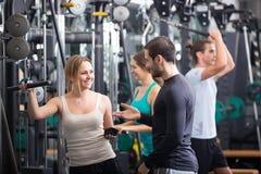 Adultos jovenes que se resuelven en club de fitness Foto de archivo libre de regalías