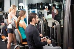 Adultos jovenes que se resuelven en club de fitness Fotos de archivo