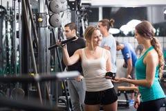 Adultos jovenes que se resuelven en club de fitness Fotografía de archivo