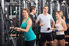 Adultos jovenes que se resuelven en club de fitness Foto de archivo