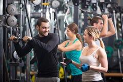 Adultos jovenes que se resuelven en club de fitness Imagenes de archivo