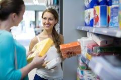 Adultos jovenes que seleccionan servilletas en tienda Imagen de archivo