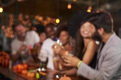 Adultos jovenes que socializan en un partido en una barra, defocussed Fotos de archivo