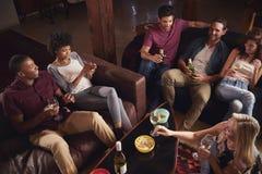 Adultos jovenes que tienen un partido en casa, visión elevada Imagen de archivo libre de regalías