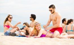Adultos jovenes que toman el sol en la playa Imágenes de archivo libres de regalías